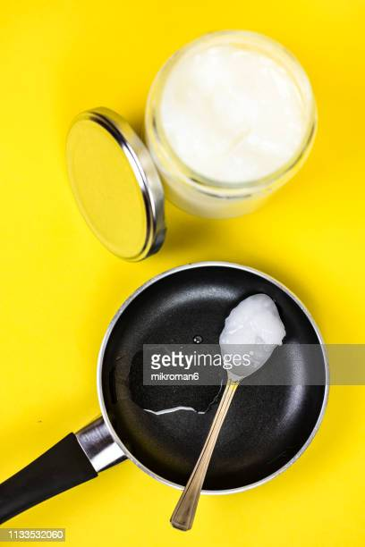 coconut oil in jar with spoon. cooking pan with coconut oil - coconut oil stock pictures, royalty-free photos & images