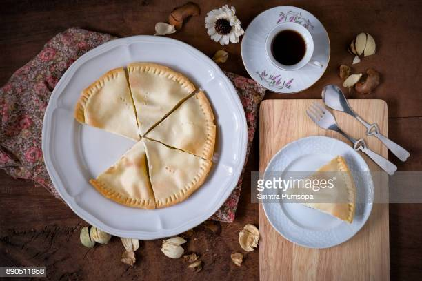 Coconut tart with a white cup of hot Espresso coffee on wooden table