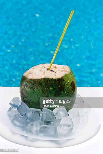 coconut water with ice cubes by the swimming pool - coconut water stock pictures, royalty-free photos & images