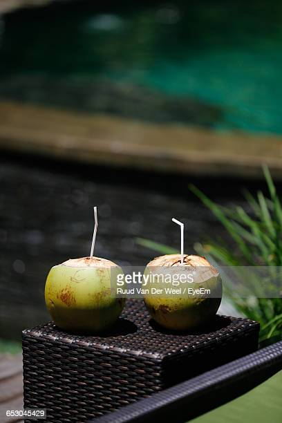 coconuts with drinking straws on stool - coconut water stock pictures, royalty-free photos & images