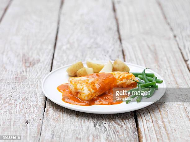 Cod fillets with a tomato and herb sauce served with green beans and new potatoes