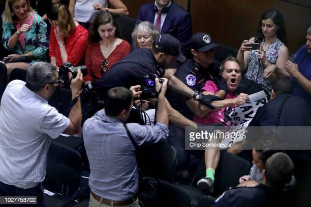 Code Pink demonstrator Tighe Barry is pulled down from a chair by a US Capitol Police officer after he interrupted the third day of Supreme Court...
