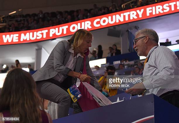 A code pink protester tries to pull up a banner as Republican presidential candidate Donald Trump arrives to speak on the last day of the Republican...