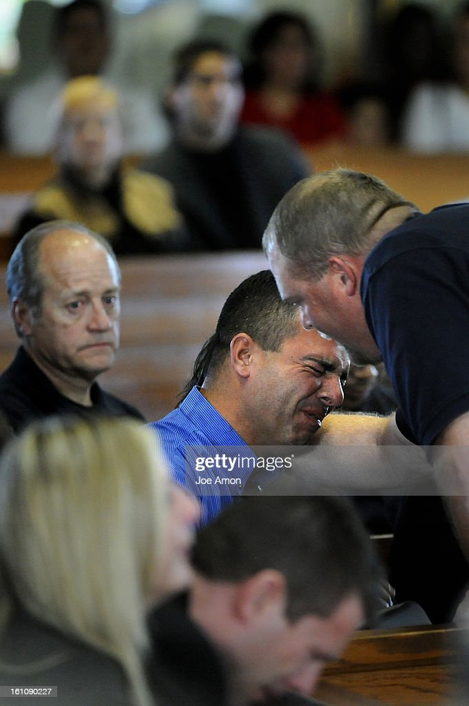 (JS) CODEMEMORIAL18f Keith Morales is hugged by his brothers supervisor Dusty Allen during a Memorial Service for Aurora code enforcement officer Rodney Morales at Queen of Peace Catholic Church in Aurora. Joe Amon/ The Denver Post : News Photo