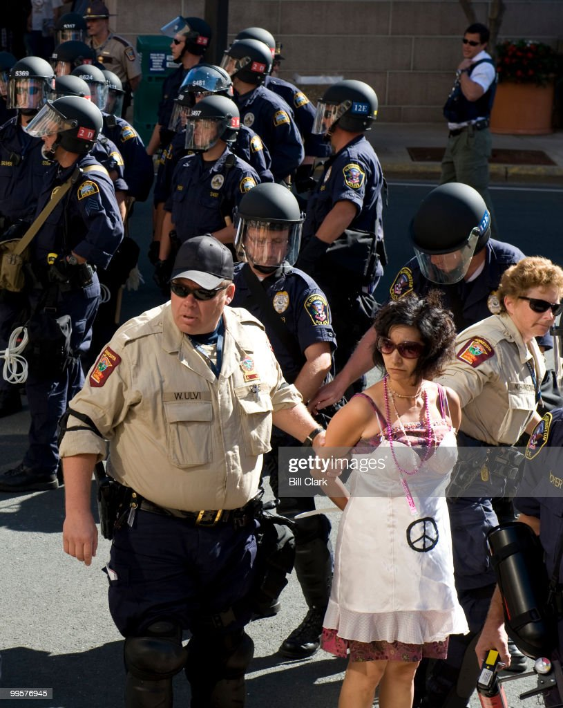 A Codepink protester is taken into custody by police at the security permimeter for the Republican National Convention at the Xcel Center in St. Paul, Minn., on Wednesday, Sept. 3, 2008.