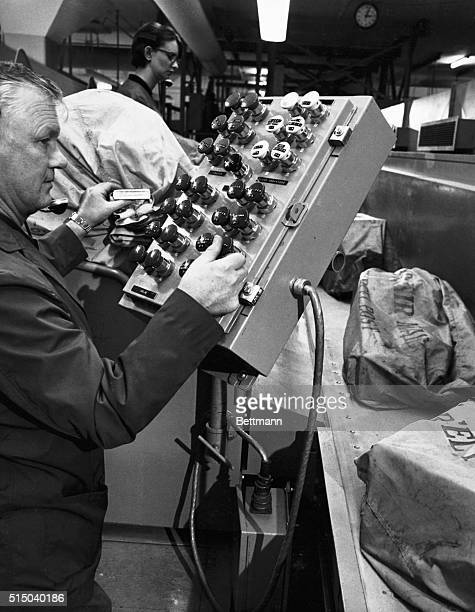 A coder at the San Francisco Air Mail Facility pushes a button at a control station to send a sack of mail on its way to a loading dock where it will...