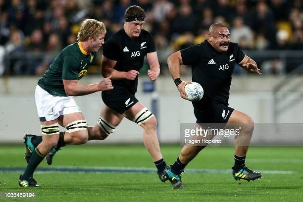Codie Taylor of New Zealand makes a break from PieterSteph du Toit of South Africa during The Rugby Championship match between the New Zealand All...