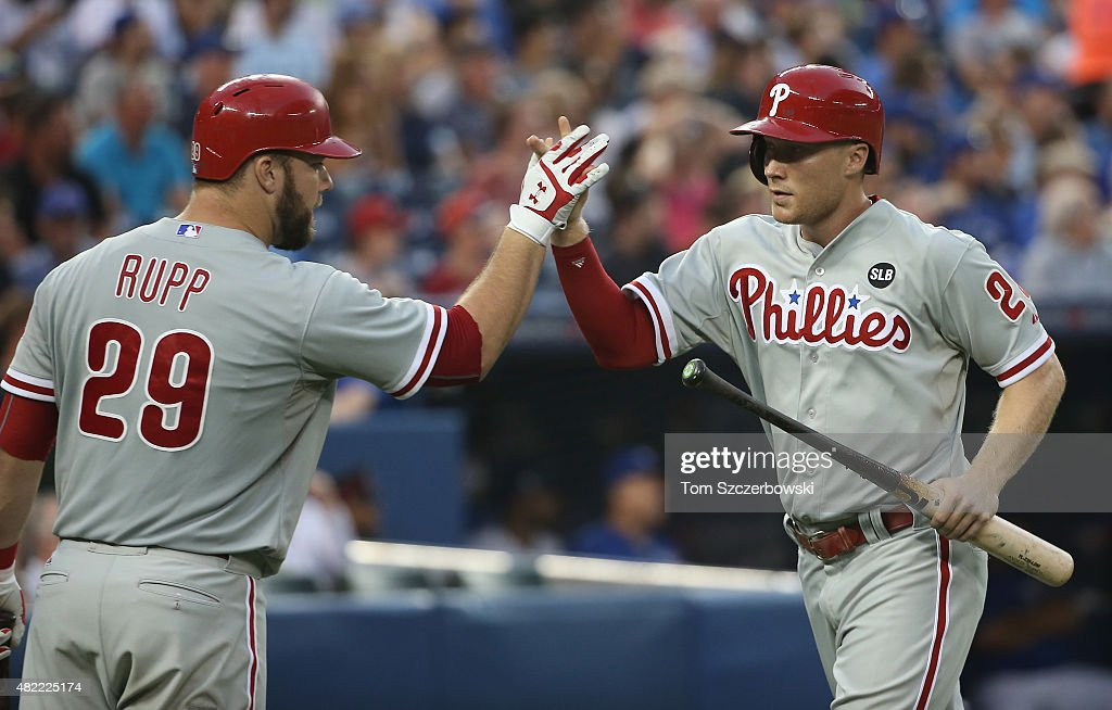 Cody Asche #25 of the Philadelphia Phillies is congratulated by Cameron Rupp #29 after scoring a run in the fifth inning during MLB game action against the Toronto Blue Jays on July 28, 2015 at Rogers Centre in Toronto, Ontario, Canada.