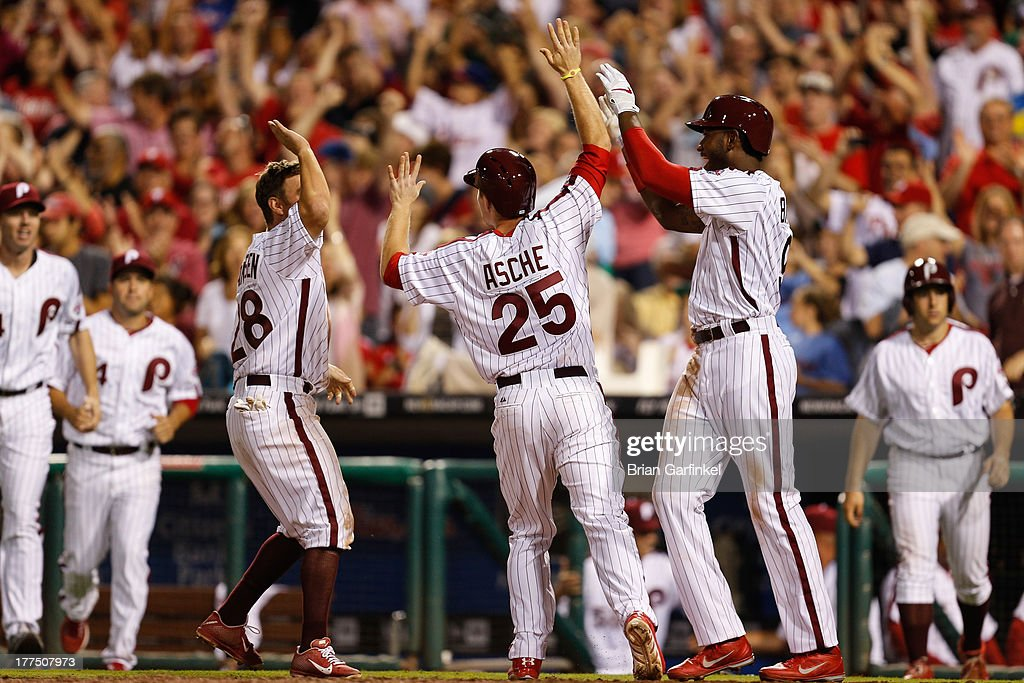 Cody Asche #25 of the Philadelphia Phillies is congratulated by teammates after scoring the game winning run off of a Chase Utley #26 walk off walk in the bottom of the ninth inning of the game against the Arizona Diamondbacks at Citizens Bank Park on August 23, 2013 in Philadelphia, Pennsylvania. The Phillies won 4-3.