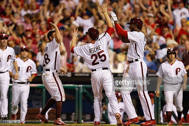 Cody Asche of the Philadelphia Phillies is congratulated by teammates after scoring the game winning run off of a Chase Utley walk off walk in the...