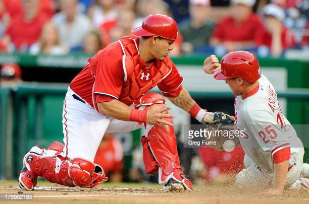 Cody Asche of the Philadelphia Phillies knocks the ball away and scores in the second inning against Wilson Ramos of the Washington Nationals at...