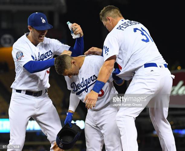 Cody Bellinger and Joc Pederson celebrate with Austin Barnes of the Los Angeles Dodgers as they defeated the Texas Rangers in the eleventh inning at...