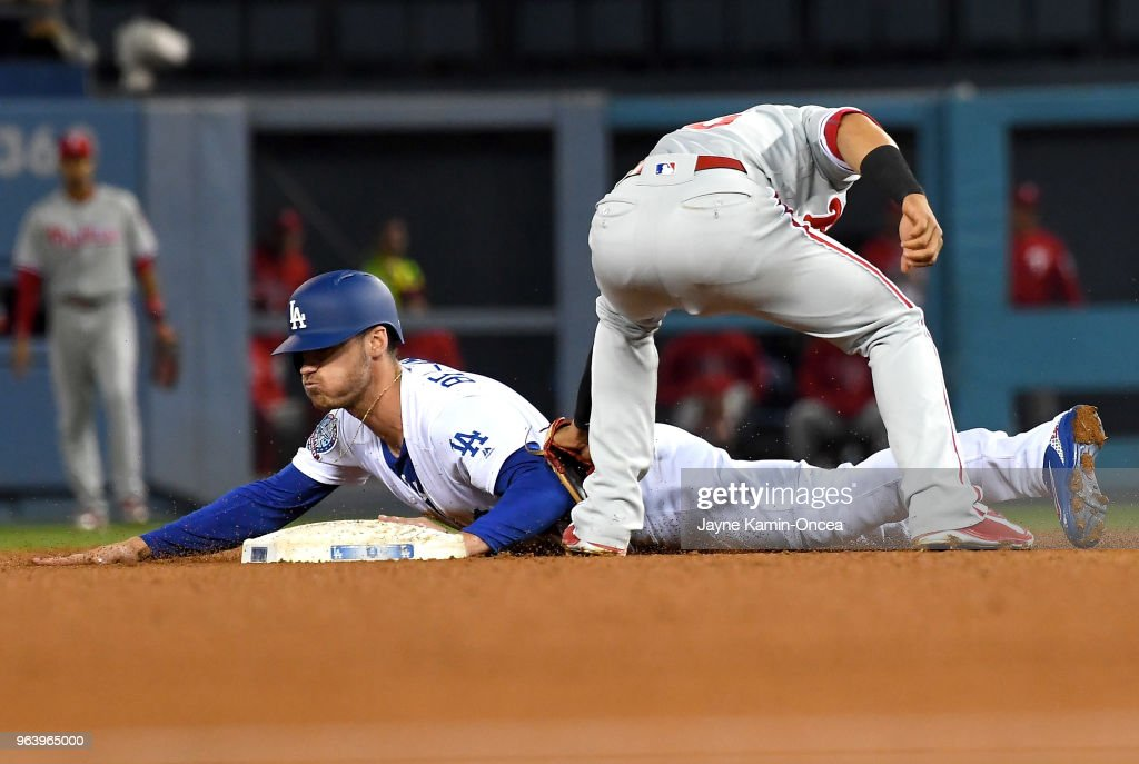 Cody Bellinger #35 of the Los Angeles Dodgers beats the throw to Cesar Hernandez #16 of the Philadelphia Phillies for a stolen base in the third inning of the game at Dodger Stadium on May 30, 2018 in Los Angeles, California.