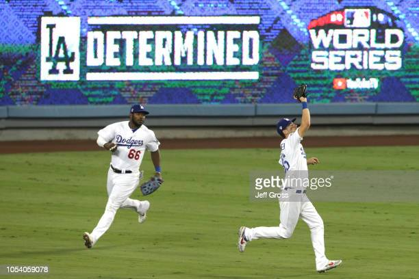 Cody Bellinger of the Los Angeles Dodgers catches a fly ball and proceeds to throw out the runner at home plate during the tenth inning against the...
