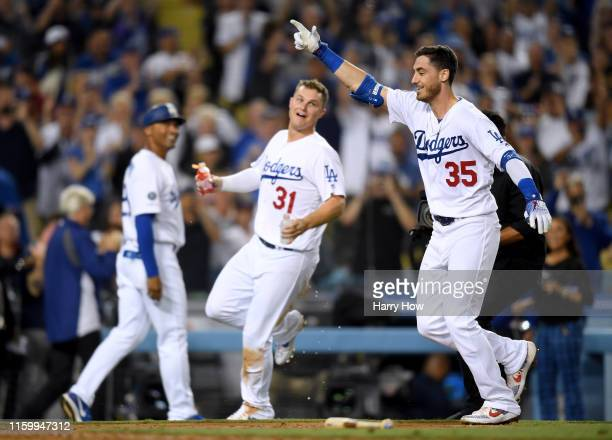 Cody Bellinger of the Los Angeles Dodgers celebrates his walk off solo homerun in front of Joc Pederson and third base coach Dino Ebel for a 54 win...
