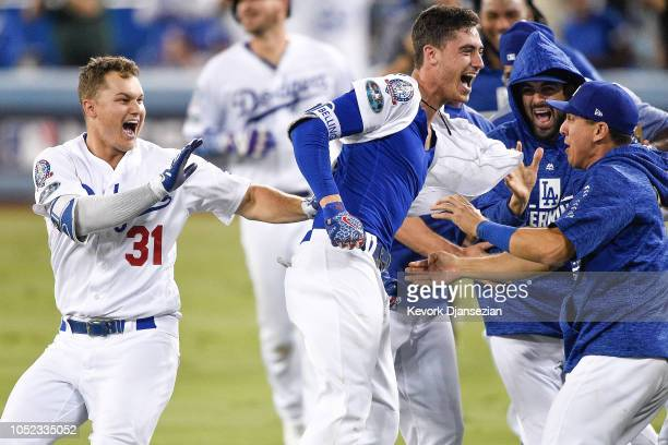 Cody Bellinger of the Los Angeles Dodgers celebrates with teammates after hitting a walkoff single in the thirteenth inning against the Milwaukee...