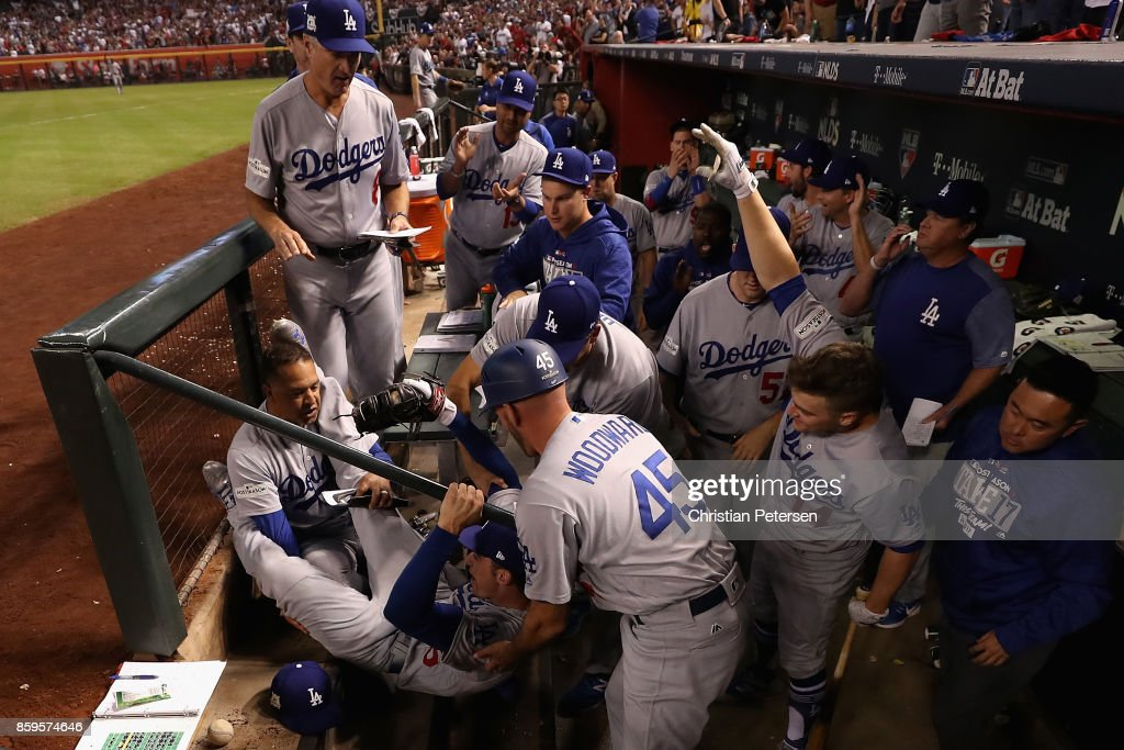 Cody Bellinger #35 of the Los Angeles Dodgers falls into the dugout over manager Dave Roberts #30 (left) and third base coach Chris Woodward #45 after catching a foul ball during the fifth inning of the National League Divisional Series game three against the Arizona Diamondbacks at Chase Field on October 9, 2017 in Phoenix, Arizona.