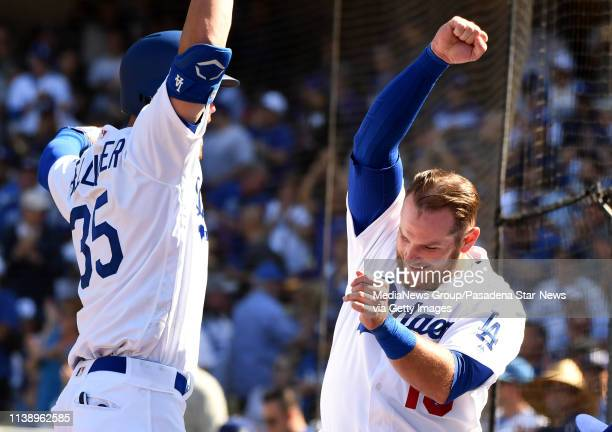 Cody Bellinger of the Los Angeles Dodgers high fives teammate Max Muncy after hitting a solo home run against the Arizona Diamondbacks in the seventh...