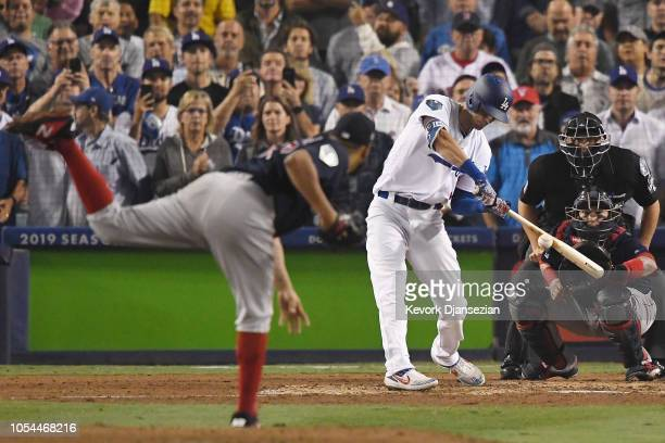 Cody Bellinger of the Los Angeles Dodgers hits a ground ball fielder's choice to first base against pitcher Eduardo Rodriguez of the Boston Red Sox...
