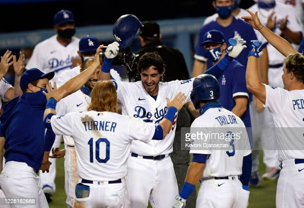 Cody Bellinger of the Los Angeles Dodgers is congratulated at home plate after hitting a game-winning walk off home run off relief pitcher Daniel...