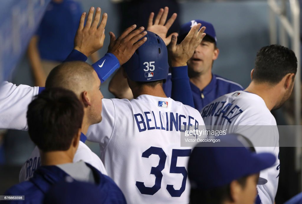 Cody Bellinger #35 of the Los Angeles Dodgers is congratulated by teammates after scoring in the second inning on a single to left field by teammate Alex Wood #57 (not in photo) during the MLB game against the San Francisco Giants at Dodger Stadium on May 2, 2017 in Los Angeles, California.