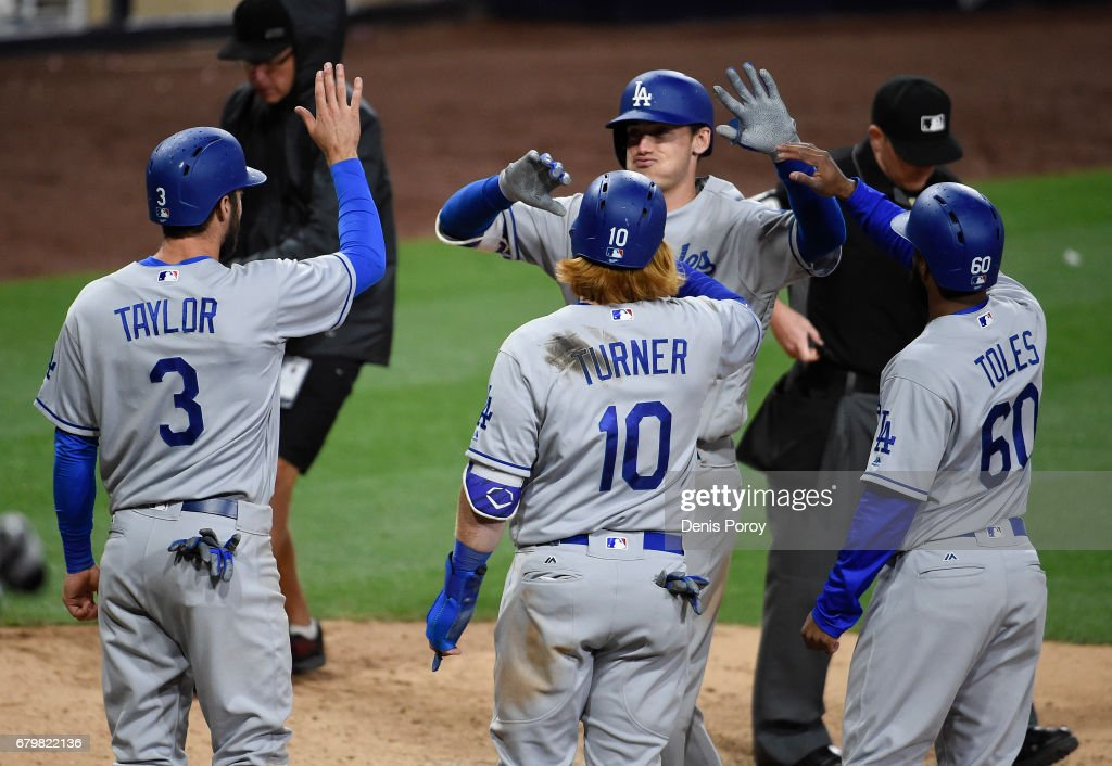 Cody Bellinger #35 of the Los Angeles Dodgers, is congratulated by Chris Taylor #3, Justin Turner #10, and Andrew Toles #60 after hitting a grand slam during the ninth inning of a baseball game against the San Diego Padres at PETCO Park on May 6, 2017 in San Diego, California.