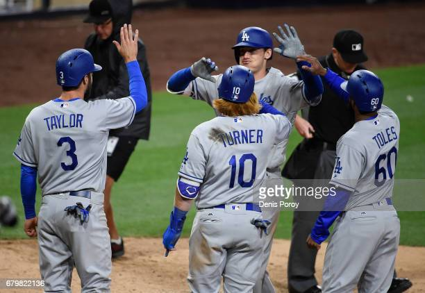 Cody Bellinger of the Los Angeles Dodgers is congratulated by Chris Taylor Justin Turner and Andrew Toles after hitting a grand slam during the ninth...
