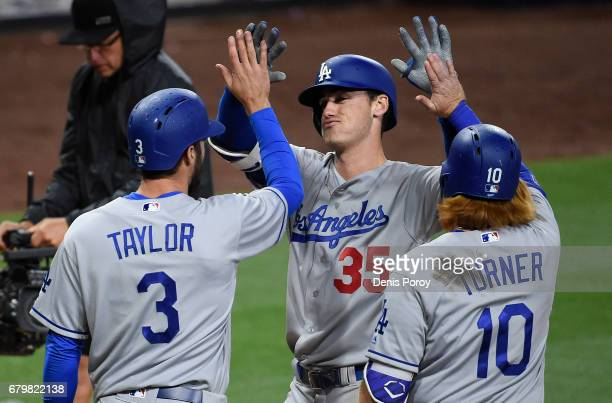 Cody Bellinger of the Los Angeles Dodgers is congratulated by Chris Taylor and Justin Turner after hitting a grand slam during the ninth inning of a...