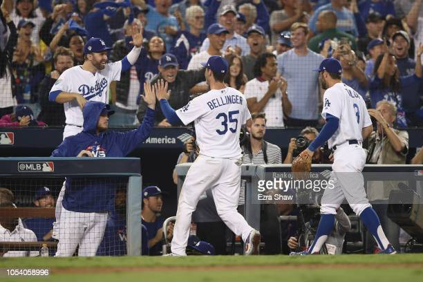Cody Bellinger of the Los Angeles Dodgers is congratulated by his teammates after throwing out the runner at home plate during the tenth inning...