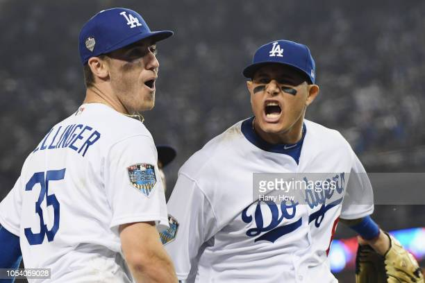 Cody Bellinger of the Los Angeles Dodgers is congratulated by his teammate Manny Machado after throwing out the runner at home plate during the tenth...