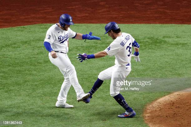 Cody Bellinger of the Los Angeles Dodgers is congratulated by Max Muncy after hitting a two run home run against the Tampa Bay Rays during the fourth...
