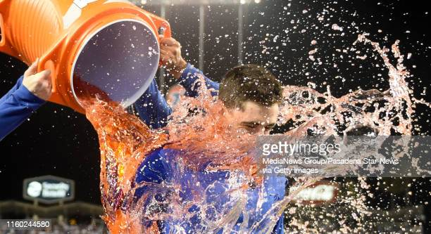 Cody Bellinger of the Los Angeles Dodgers is doused with sports drink by teammate Matt Beaty after hitting a walk off solo home run to defeat the...