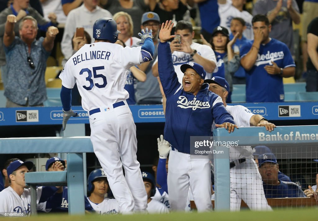 Cody Bellinger #35 of the Los Angeles Dodgers is greeted by manager Dave Roberts as he returns to the dugout after hitting a solo home run in the ninth inning against the Philadelphia Phillies at Dodger Stadium on April 29, 2017 in Los Angeles, California. It was Bellinger's second home run of the night with the first being his first Major League home run. It was also the second of three homes in a row to lead off the ninth and bring the Dodgers back to the game at 5-5. The Dodgers went on to win 6-5.