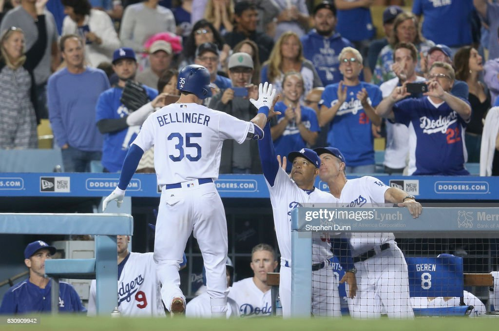 Cody Bellinger #35 of the Los Angeles Dodgers is greeted manager Dave Roberts (C) and coach Bob Geren as he returns to the dugout after hitting a solo home run in the seventh inning past catcher Austin Hedges #18 of the San Diego Padres at Dodger Stadium on August 12, 2017 in Los Angeles, California.