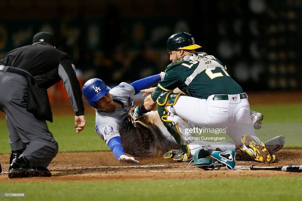 Cody Bellinger #35 of the Los Angeles Dodgers is tagged out at home plate by catcher Jonathan Lucroy #21 of the Oakland Athletics in the sixth inning at Oakland Alameda Coliseum on August 7, 2018 in Oakland, California.