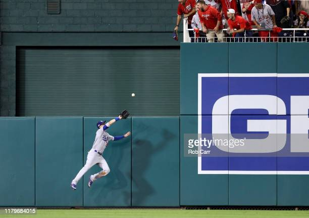 Cody Bellinger of the Los Angeles Dodgers leaps to catch a sacrifice fly hit by Anthony Rendon of the Washington Nationals to drive in a run in the...