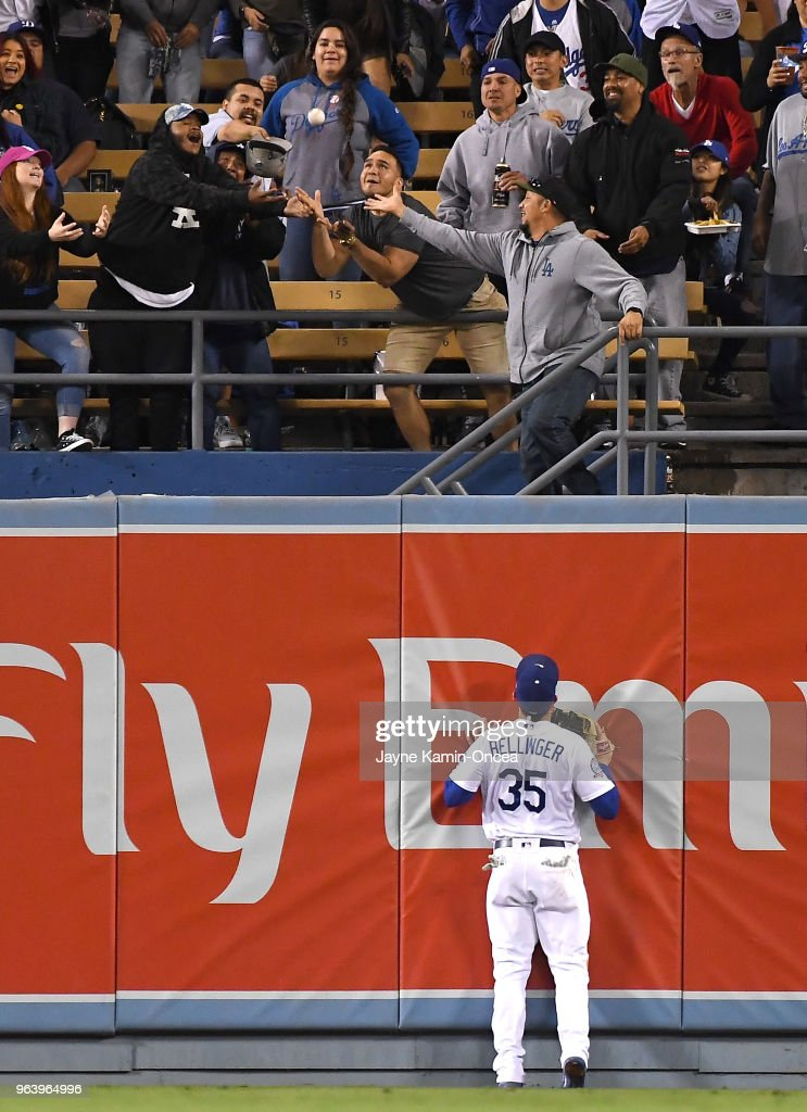 Cody Bellinger #35 of the Los Angeles Dodgers looks on as fans attempt to catch the home run ball hit by Nick Williams #5 of the Philadelphia Phillies in the seventh inning of the game at Dodger Stadium on May 30, 2018 in Los Angeles, California.