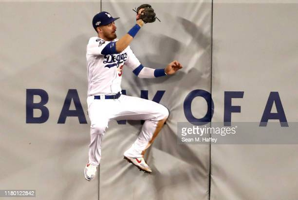 Cody Bellinger of the Los Angeles Dodgers makes a catch on the wall on a hit by Howie Kendrick of the Washington Nationals for an out in the fourth...