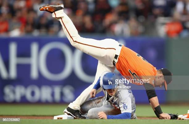 Cody Bellinger of the Los Angeles Dodgers prevents Joe Panik of the San Francisco Giants from throwing the ball to first base in the second inning at...