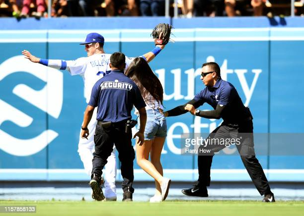 Cody Bellinger of the Los Angeles Dodgers reacts as a fan chases after him on the field during the ninth inning against the Colorado Rockies at...