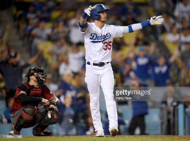 Cody Bellinger of the Los Angeles Dodgers reacts to his walk off solo homerun in front of Carson Kelly of the Arizona Diamondbacks for a 54 win...