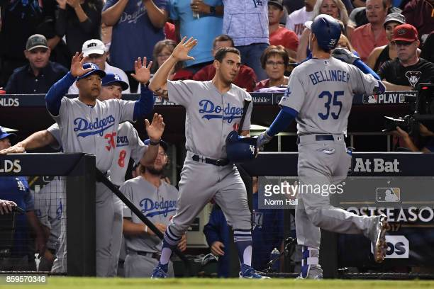 Cody Bellinger of the Los Angeles Dodgers reacts with team mate Austin Barnes and manager Dave Roberts after hitting a one run home run during the...