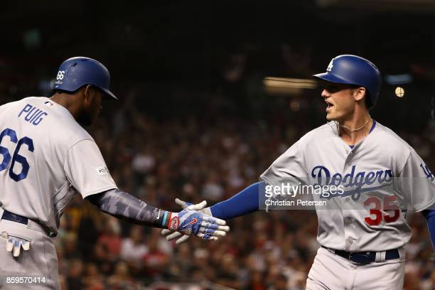 Cody Bellinger of the Los Angeles Dodgers reacts with team mate Yasiel Puig after hitting a one run home run during the fifth inning of the National...