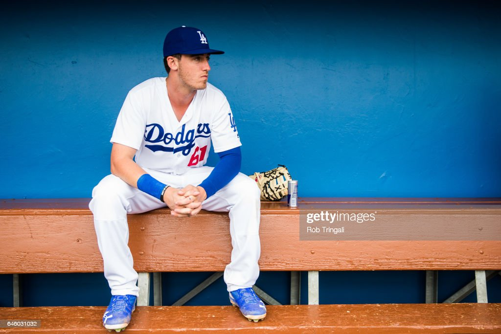 Cody Bellinger #61 of the Los Angeles Dodgers sits in the dugout before a spring training game against the Colorado Rockies at Camelback Ranch on February 27, 2017 in Glendale, Arizona.