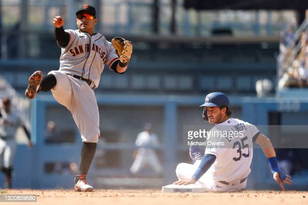 Cody Bellinger of the Los Angeles Dodgers slides into second base as Donovan Solano of the San Francisco Giants attempts to throw to first for a...