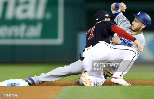 Cody Bellinger of the Los Angeles Dodgers steals second base ahead outfield Trea Turner of the Washington Nationals in the fourth inning of game four...