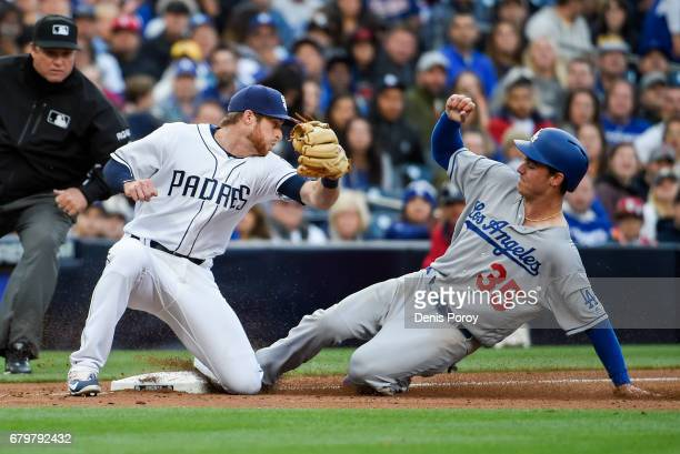 Cody Bellinger of the Los Angeles Dodgers steals third base ahead of the tag of Cory Spangenberg of the San Diego Padres during the fourth inning of...