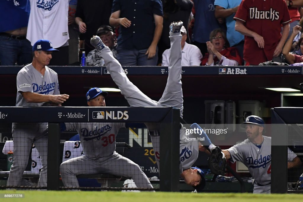Cody Bellinger #35 of the Los Angeles Dodgers tumbles into the dugout after catching a foul ball during the fifth inning of the National League Divisional Series game three against the Arizona Diamondbacks at Chase Field on October 9, 2017 in Phoenix, Arizona.