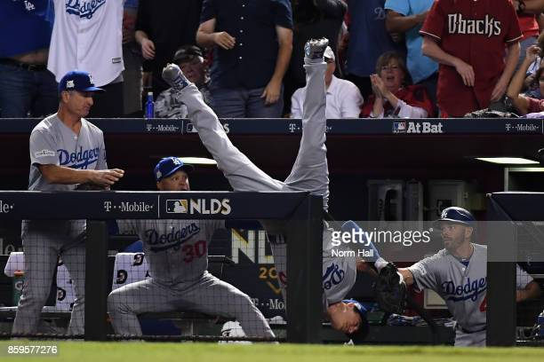 Cody Bellinger of the Los Angeles Dodgers tumbles into the dugout after catching a foul ball during the fifth inning of the National League...