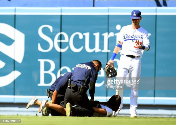 Cody Bellinger of the Los Angeles Dodgers waves to a fan as she is handcuffed by security for running onto the field during the ninth inning against...